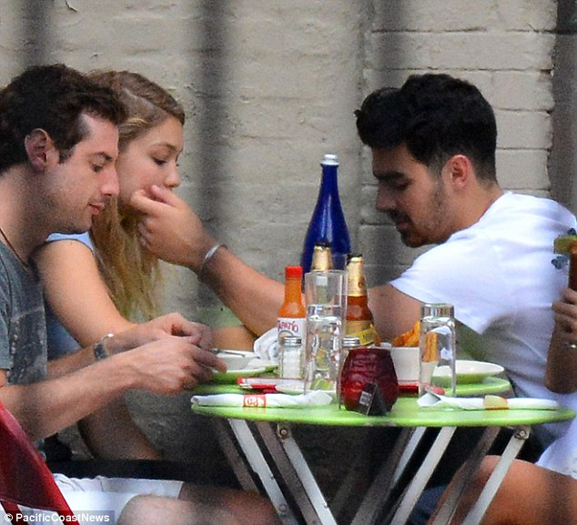 So cozy: The Jonas brother didn't even look up as he touched his amour