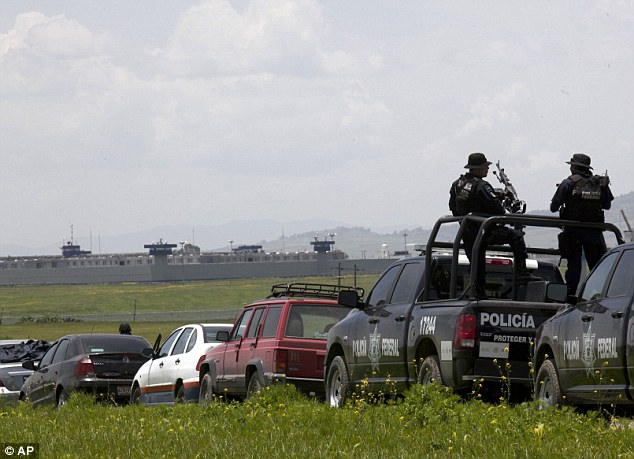 """Search continues:Federal Police man their weapons aboard a pick up truck, near the half-built house where drug lord Joaquin """"El Chapo"""" Guzman made his escape through a tunnel from the Altiplano maximum security prison in Almoloya, west of Mexico City"""