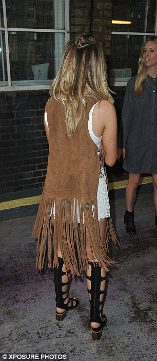 Boho chic: Perrie showed off her bronzed figure in a white crop top and lace hot pants which she teamed with a sleeveless fringed duster coat and sexy, knee-high gladiator sandals