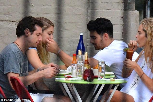 Double date: The couple enjoyed an al fresco dinner with friends as Joe was seen softly brushing Gigi's cheek