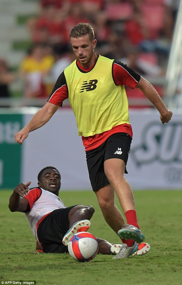 Kolo Toure slides in to try and win the ball from Henderson as the players prepared for Tuesday's game