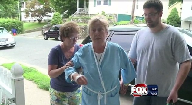 Nursing broken ribs: Kathleen Danise, 60,  is seen returning home from the hospital on Sunday after she was catapulted out of her beach chair at Salty Brine Beach in Narraganset into the rock jetty on Saturday