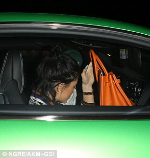 Date night:Kylie, 17, hid her face for view with her bright orange Birkin handbag but it was clear to see she had taken out her cornrows since the spat and she was sporting her usual glamorous make-up look