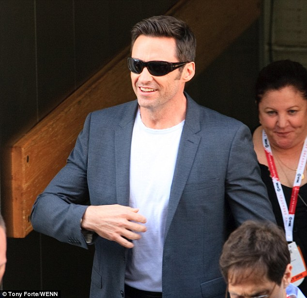 Shades of grey: Hugh hid his chiseled face behind a pair of dark shades as he arrived at Comic-Con