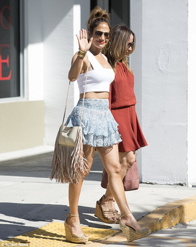 Dare to bare: Jennifer Lopez flaunted her washboard stomach in a white crop top as she spent the day shopping with a female friend in Miami on Sunday