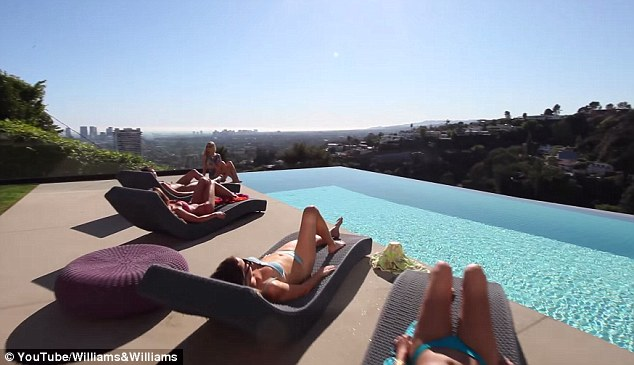 Pool life: The home's infinity pool, with views over the Hollywood hills, is shown off surrounded by the women who relax in bikinis in the slick footage