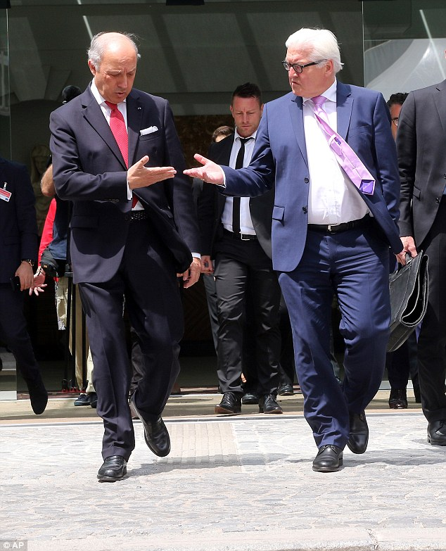 French Foreign Minister Laurent Fabius and German Foreign Minister Frank-Walter Steinmeier arrive for a press briefing in front of Palais Coburg, Vienna where closed-door nuclear talks with Iran continue
