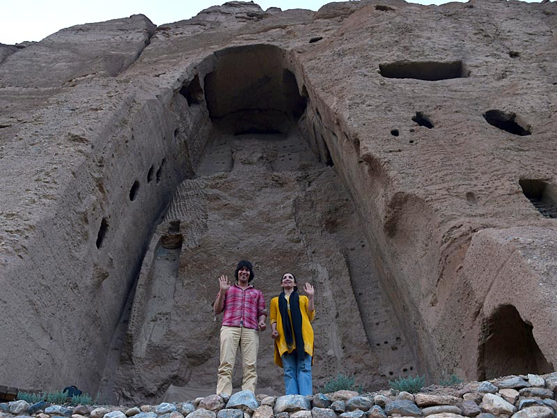 An Afghan couple poses in front of the empty site of two Buddha statues, which were destroyed by the Taliban, in Bamiyan.(AFP Photo)