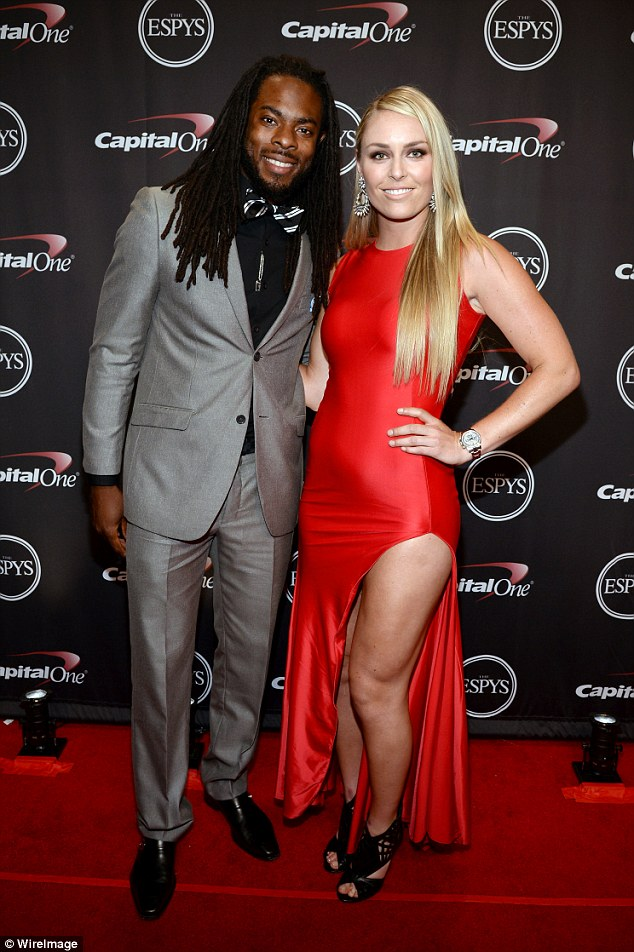 Red hot: At Wednesday night's Lindsey, pictured with Seahawks cornerback Richard Sherman, looked stunning in a figure-hugging floor-length scarlet gown