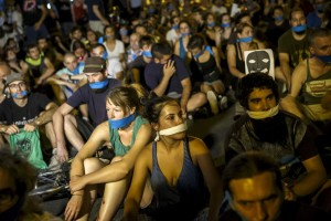 """Demonstrators with their mouths taped sit outside the Spanish parliament during a protest against Spanish government's new security law in central Madrid, Spain, early July 1, 2015. Spanish government's new security law, which toughens fines for unauthorised street protests, comes into effect July 1. Critics consider it a violation of the right to protest and a limit to free expression and have labeled it """"Ley Mordaza"""" (Gag Law). REUTERS/Juan Medina - RTX1IIKE"""