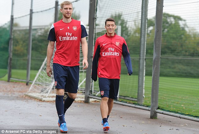 Compatriots: Ozil (right) walking with his fellow Germany star Per Mertesacker