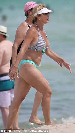 Beach belle: Wearing a black and white stripey bikini top and turquoise blue bottoms, the 53-year-old kept the sun off her face with a white visor and a pair of sunglasses