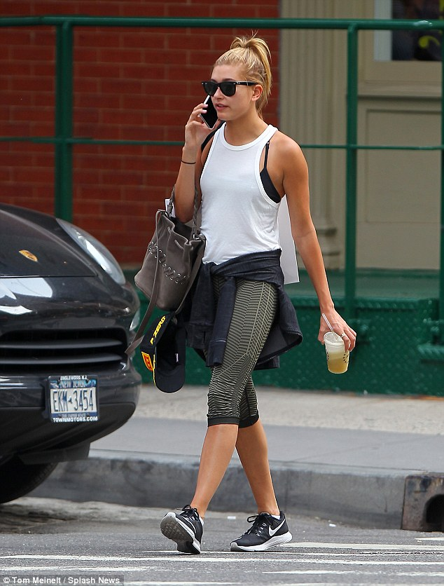 Stepping out: Hailey looked every inch the gym bunny in a white racer back vest top and stripped leggings which she teamed with Nike trainers and a black hoody tied around her waist