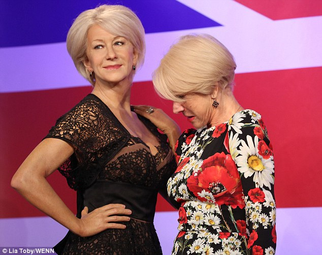 Like what you see? Helen Mirren peers into her waxwork's cleavage atMadame Tussauds London on Thursday during a display in honour of her 70th birthday on July 26