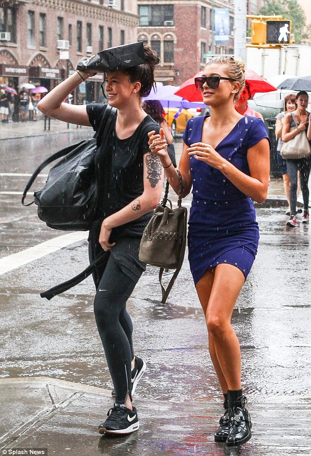 Flash flood: Ireland and cousin Hailey giggle despite the miserable conditions