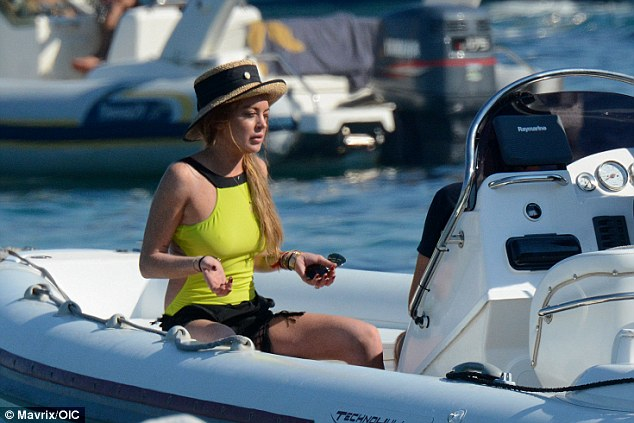 Summer holiday: Lindsay Lohan stripped down to a super bright swimsuit during another day in Mykonos, Greece on Tuesday where she's enjoying a sun-soaked break