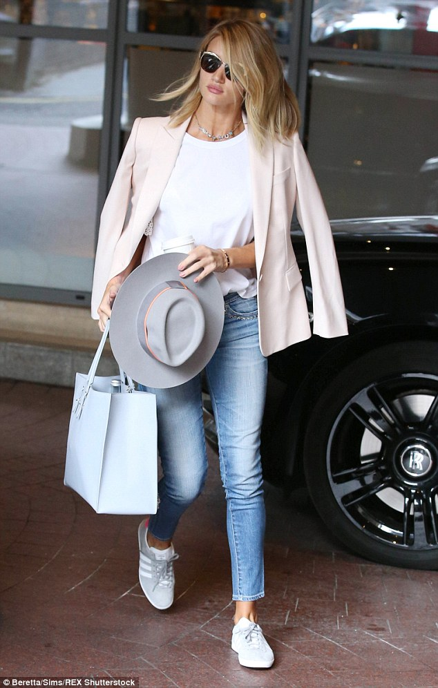 Simple style stunner: The beauty teamed her jeans with a white t-shirt and a pale pink blazer worn caped over her shoulders