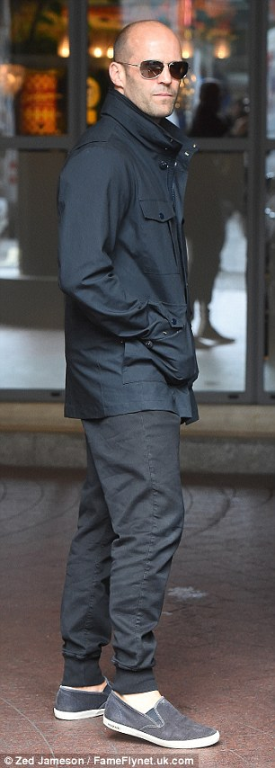 Sticking by her side: Rosie's handsome boyfriend Jason Statham, 48, cut a far more low-key figure as he left the building with her, covering up in nondescript dark clothing and shades