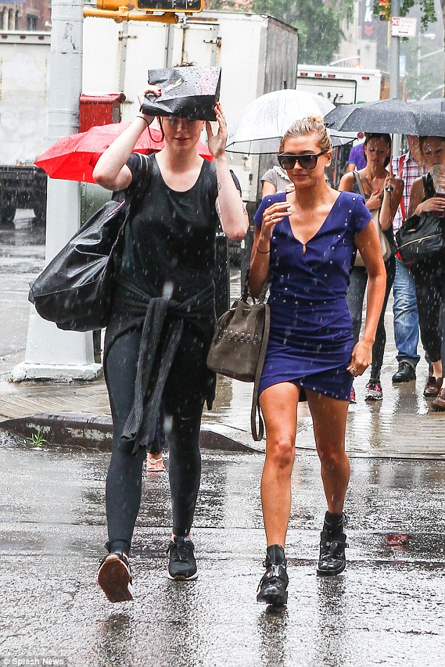 Rainy day: Ireland, 19, tried to use her tiny shopping bag for shelter