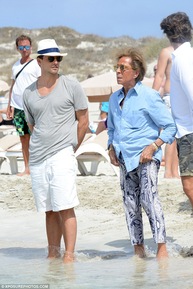 Having a paddle: Valentino dipped his toes into the waters, pulling up his trousers so as not to ruin them
