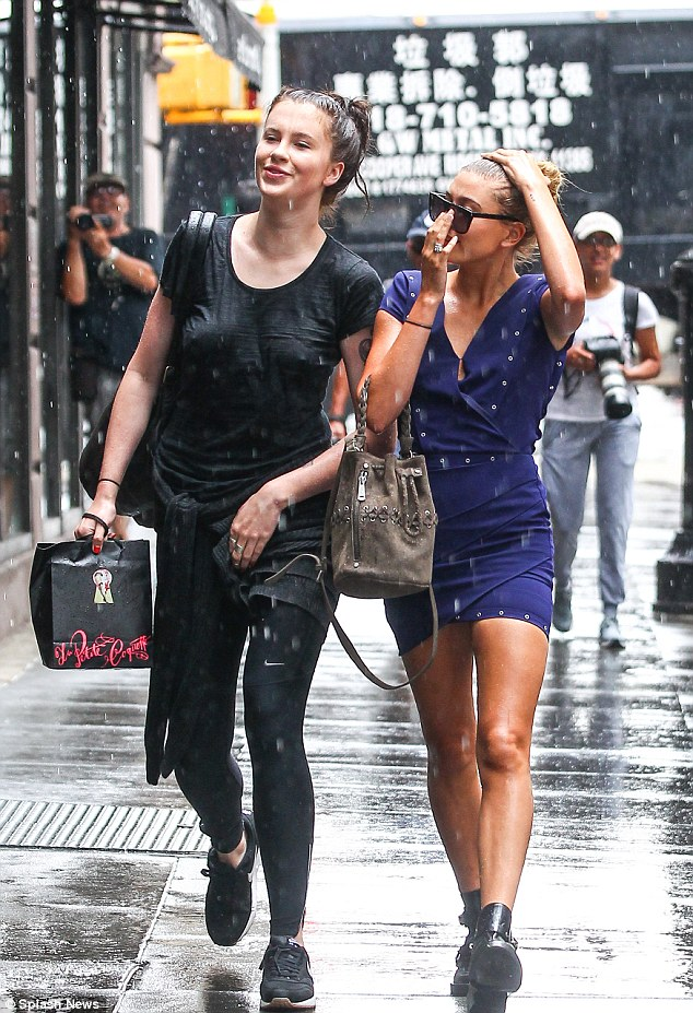Funny side: The model seemed to get a kick out of the sudden storm even though her thin T-shirt was sopping wet