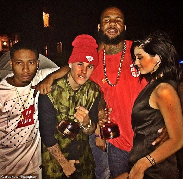 Not yet 21: Kylie (far right) celebrated turning 17 at an LA club with (from left) Tyga, Justin Bieber and The Game, the last two who were holding bottles of hard liquor