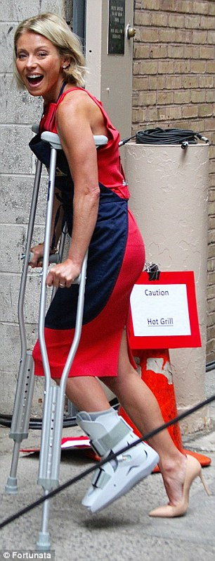 Balancing act: Wearing a beige pump on her uninjured foot, Kelly was able to get around on crutches