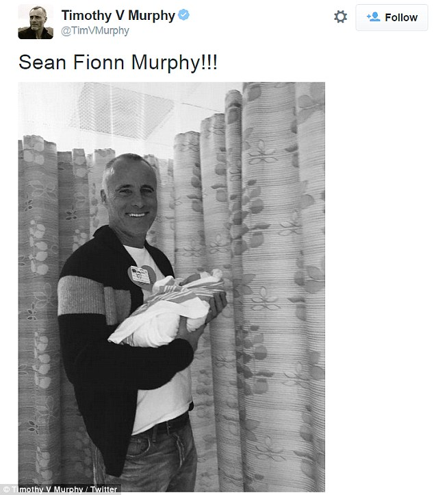 Proud parent: Timothy beamed as he held the new baby boy