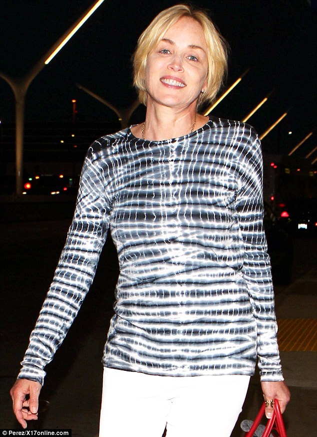 Glimmer gal: Sharon Stone arrived at Los Angeles International Airport on Thursday in a shimmering top