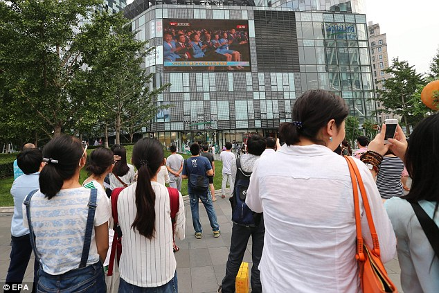 Spectators gather in China outside a Beijing shopping mall to watch the announcement on the 2022 Games
