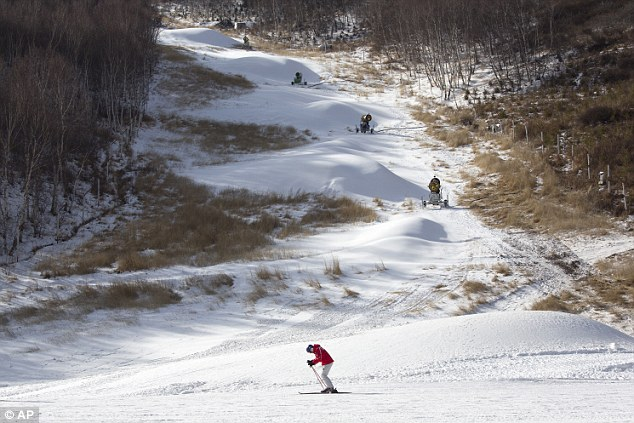 A skier passes by snow machines on the slopes of the Chongli ski resort in Hebei province where the Nordic skiing, ski jumping, and other outdoor Olympic events are scheduled to be held at the 2022 Winter Olympics