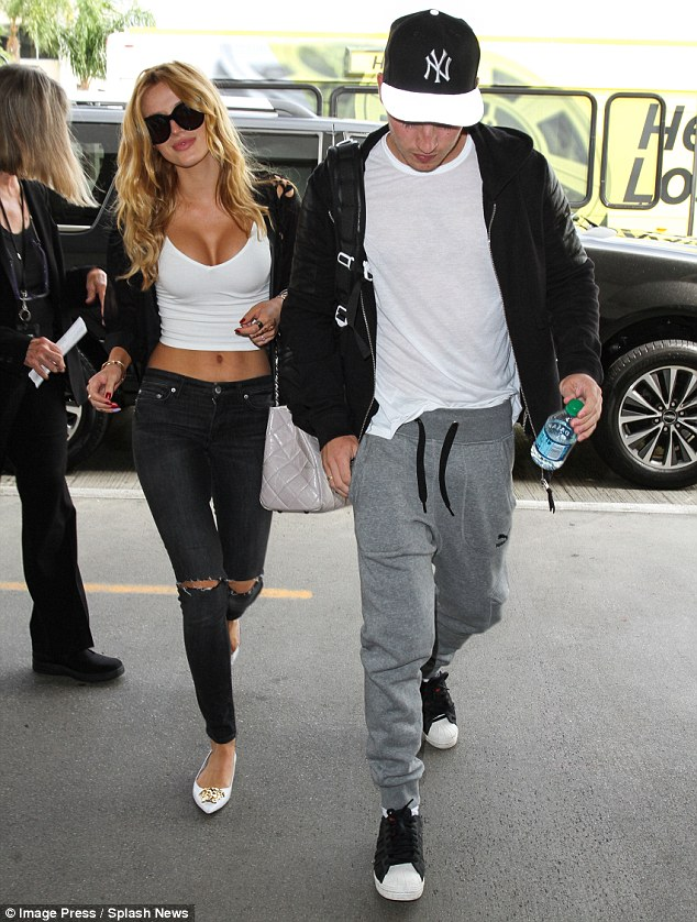 Loved up: Bella and her beau Gregg Sulkin, right, touched down at LAX on Wednesday