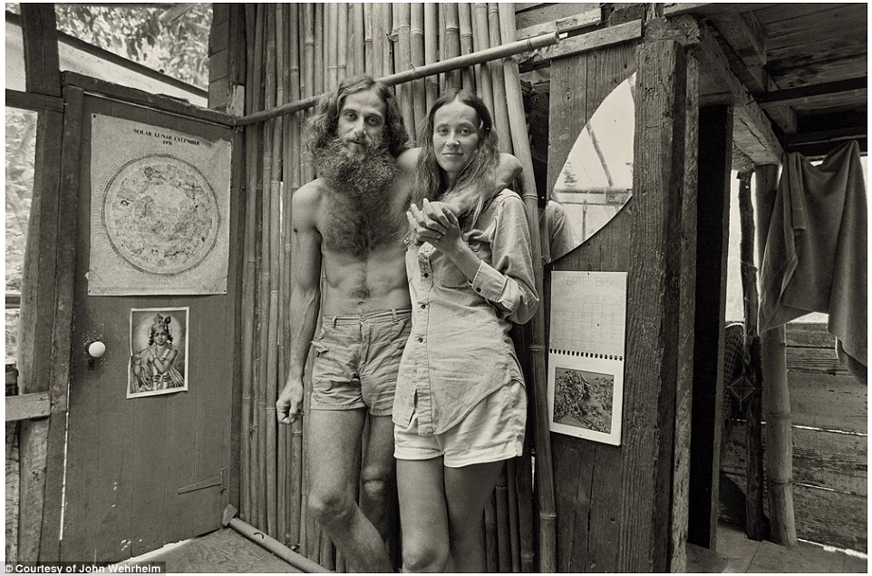 Portrait of love: A happy couple embrace and smile for the cameras inside a hut in Taylor Camp