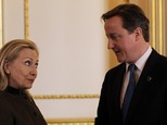 Prime Minister David Cameron talks with Hillary Clinton during a conference in London