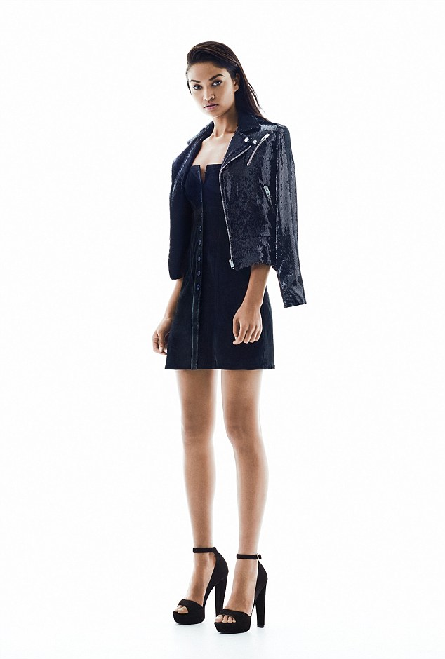 Black on black on black! The model pairs a glimmering jacket with a dress and eyecatching heels