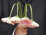 Man holding drooping flowers