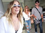 LeAnn Rimes in ripped jeans and white sweater flying solo arriving at  LAX. Monday, August 3, 2015. X17online.com