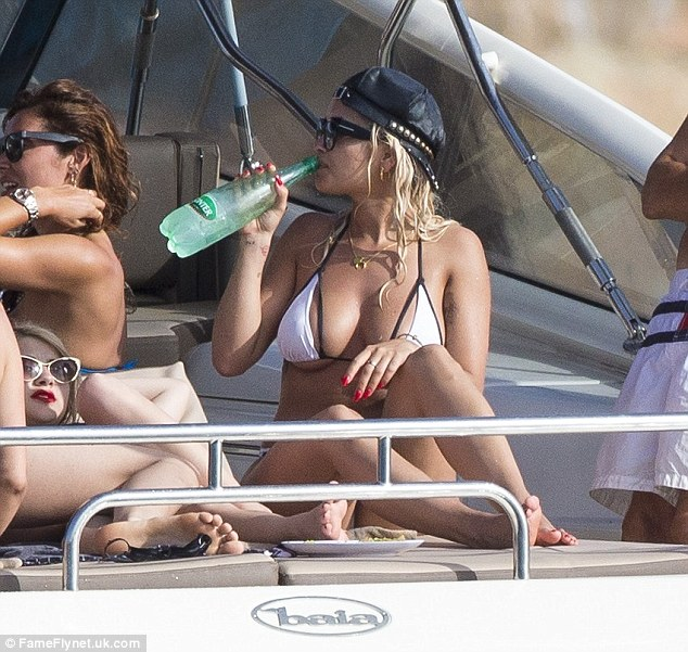 Kicking back: Rita cooled off with an ice cold drink as she lounged on deck with her pals
