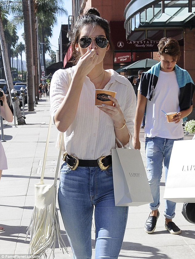 Street chic: Both ladies matched in high-waisted denim with Kendall adding a white button-down to the look