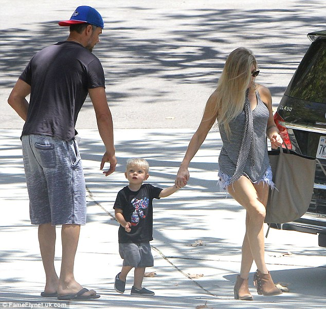 Both hands please: The Transformers actor reversed his baseball cap and kept it casual in long shorts and flip-flops, while his son had a striking resemblance in a matching black tee with grey shorts