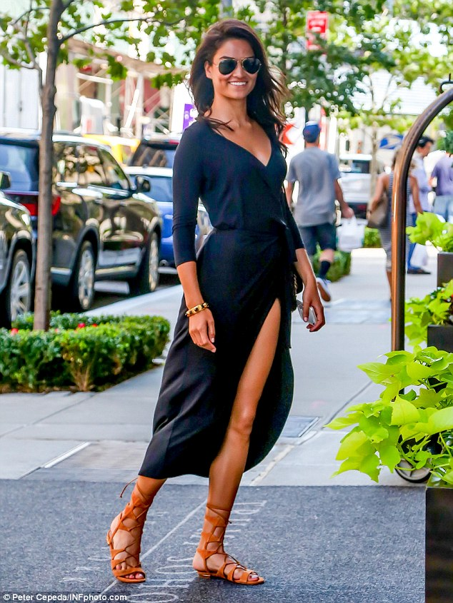 Racy: The 24-year-oldslipped her Victoria's Secret figure into a floaty navy frock with a plunging neckline and daring thigh-high split