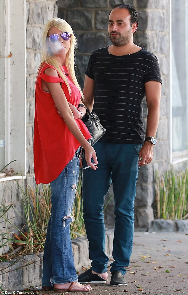 Smoking: Tara Reid, 39, was spotted puffing on a cigarette as she left lunch with a friend in Beverly Hills on Monday; the actress revealed her extremely thin arms in a sleeveless red top