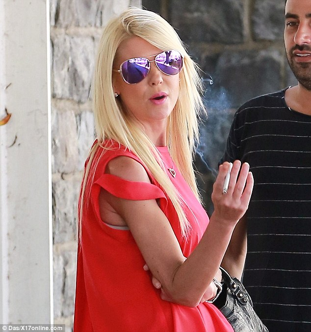 Sleek: Her ash-blonde locks were straightened and left to hang loose around her shoulders as she smoked on the outdoor sidewalk while waiting for her car