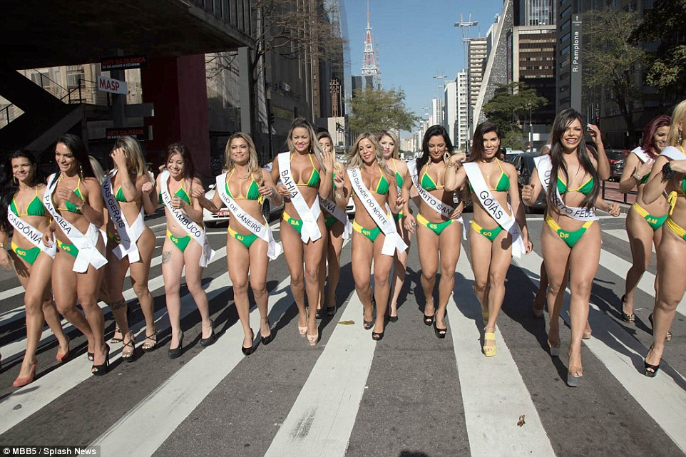 Body proud: Each glamorous girl wears a thin white sash, to show which region of Brazil they are representing, as well as a skimpy bikini and towering heels