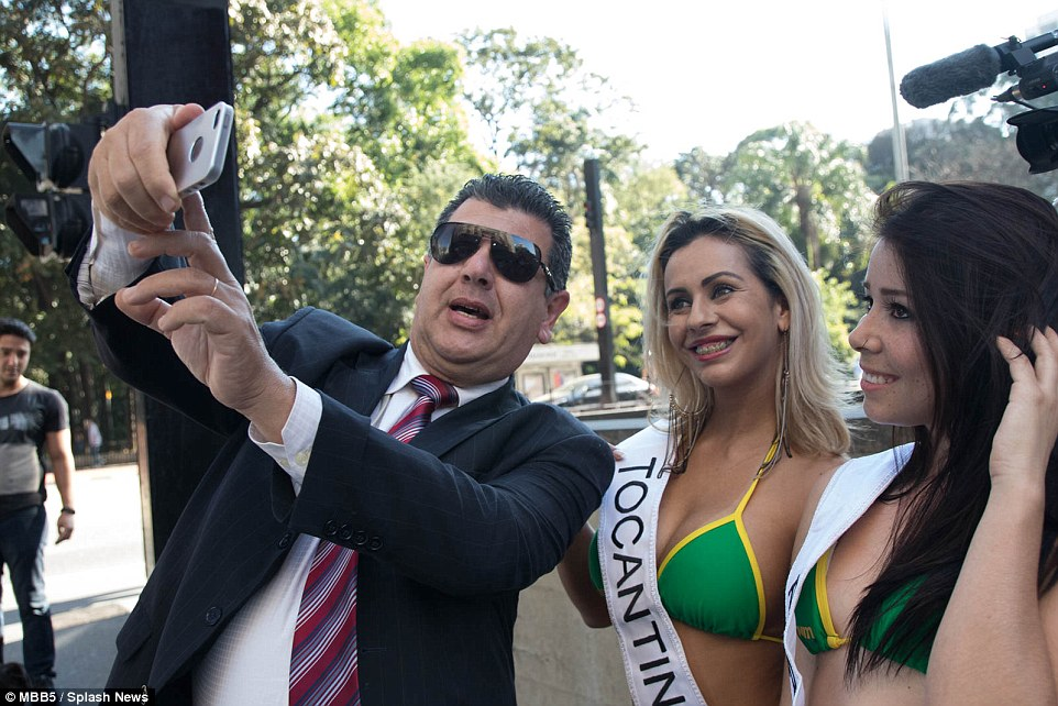 Posing: One smartly dressed gentleman poses with two of the contestants for an all important selfie