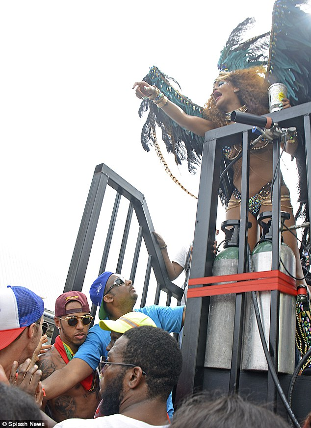 Close: Lewis Hamilton, wearing purple cap, is pictured with Rihanna, top right, at Barbados' Crop Over festival