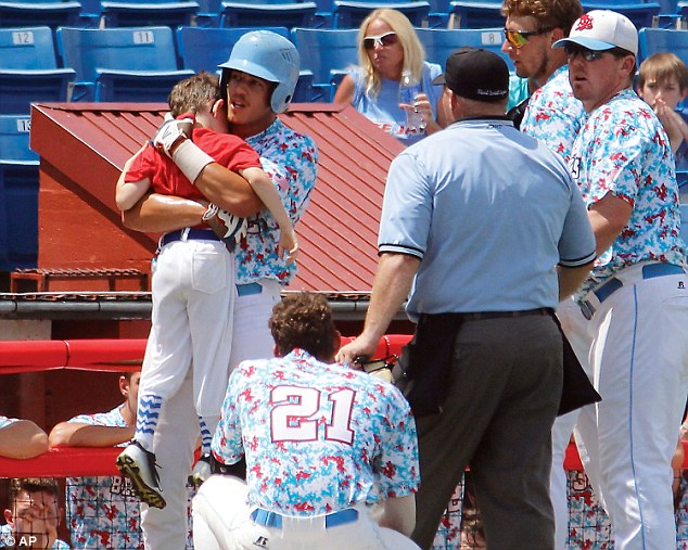 Heart-wrenching: Nine-year-old bat boy Kaiser is seen being hugged by Liberal Bee Jays outfielder Gavin Wehby in Kansas on Saturday - just seconds after he was struck