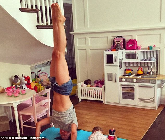 Toned: Baldwin Instagrammed a photo of herself performing a hand stand beside her daughter Carmen in late July