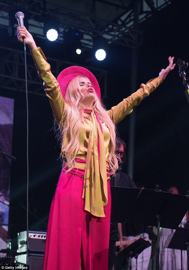 Quick change: The chart-topper cracked out her third outfit of the day for her performance, this time choosing a mustard yellow and hot pink satin ensemble
