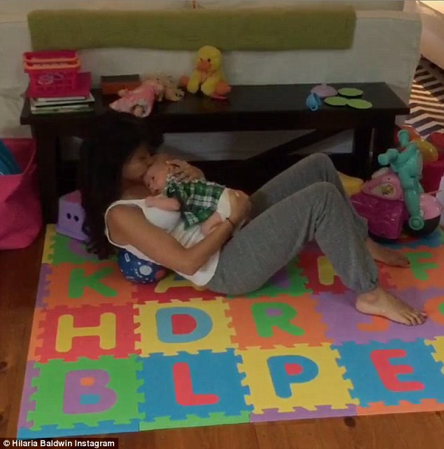 Multi-tasking: Hilaria Baldwin Instagrammed a video of herself performing a series of crunches while cradling her infant son Rafael on Tuesday